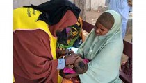 Somalian woman vaccinating child against Polio